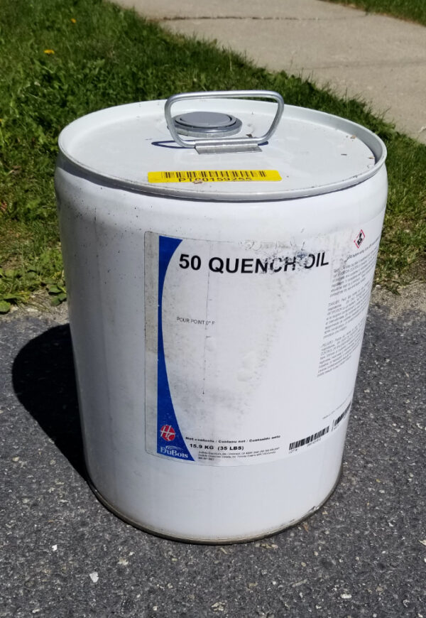 large white chemical container with the label reading 50 quench oil