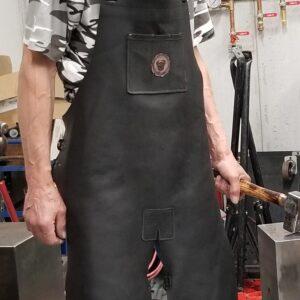 Man wearing a blacksmith apron holding a hammer